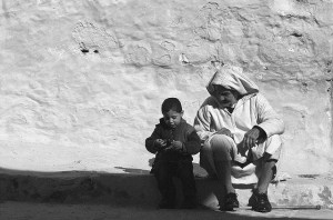 An older man and a little boy sit on the ground in front of a white stucco wall.