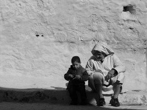 An older man and a little boy sit on the ground in front of a wall talking.