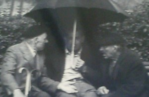 Three old men beneath an umbrella in the rain chatting intently.