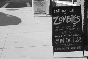 Sandwich board outside coffee shop advertises date and time for zombie gathering and walk.