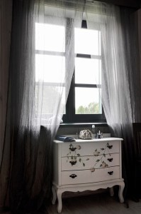 white dresser before a window with filmy white curtains