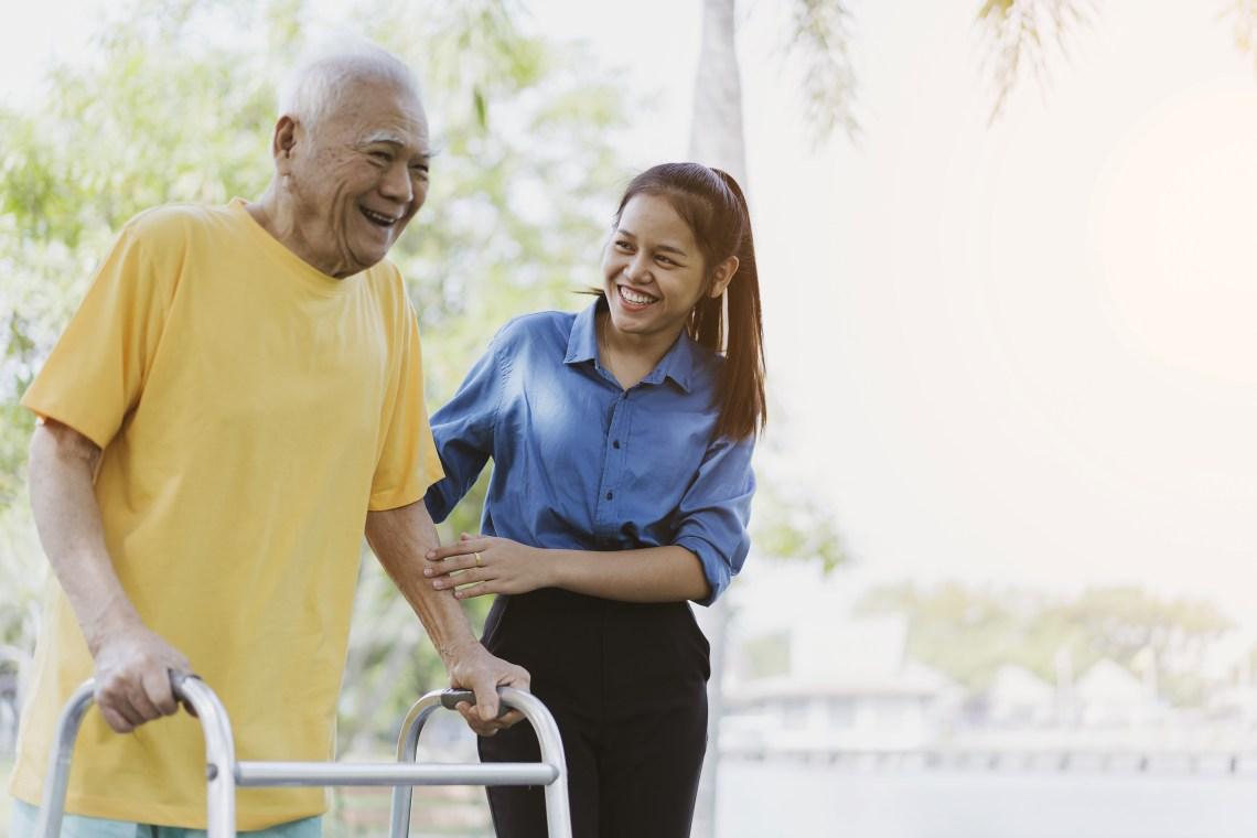 Woman assisting older gentleman with walker