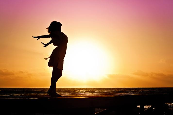A woman is seen holding her arms outstretched behind her in front of a setting sun.