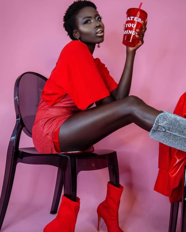 Olivia Sang | My Love For Modelling And The Realities Of It - Lysa Magazine model Olivia Sang posing with a cup written water you doing as she is seated on a chair that's wearing red boots