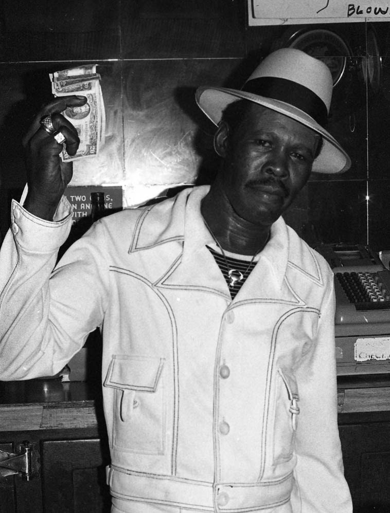 """Smokey Wilson showing us the cabbage ---- behind the bar at his Pioneer Club, one of my watering holes, 88th & Vermont, Watts, Los Angeles -- 1978 photo by Mark Weber ---- Smokey could really tear up a guitar, this was blues of the hard-bitten and gritty variety,  a beer & wine establishment he kept a whisky bottle in  his office so that during breaks (when he wasn't on stage) we'd go back for a little nip ---- When he came  to Albuquerque on tour in 1995 playing at El Madrid I hadn't seen Smoke in many years and when  I walked up he shouted """"Johnny Walker Red! Where you been?"""""""