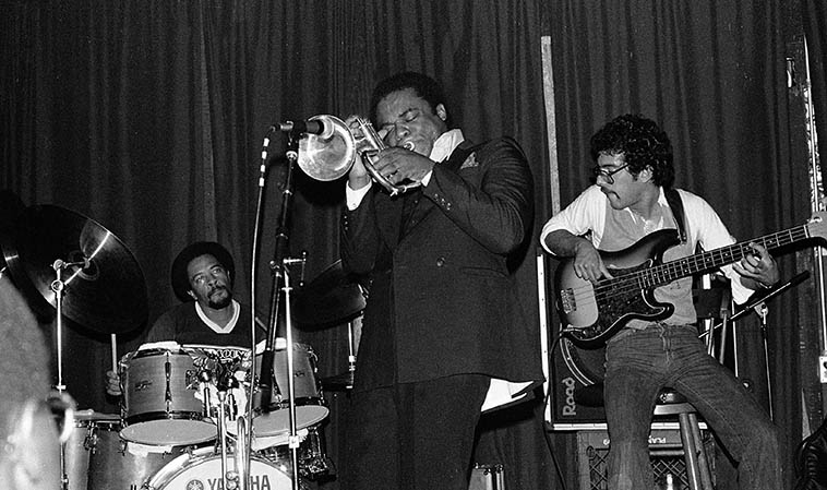 Freddie Hubbard and his band at a little short-lived venue in Claremont, California, called Orient Express -- Carl Burnett, drums; Larry Klein, elec-bass; (Billy Childs, keyboard) -- October 1, 1979 -- photo by Mark Weber ---- I didn't much care for the sound values that Freddie was using on his records during this period (some sort of pop-disco-funk) but holy geezus, to catch him live those years was something else -- He really went for it, just dug in and swung hard -- In that, he was like Art Pepper, they both played as if hellhounds were on their trail, as if redemption might be in every tune, it was harrowing, playing as if their life depended on it, and maybe it did?