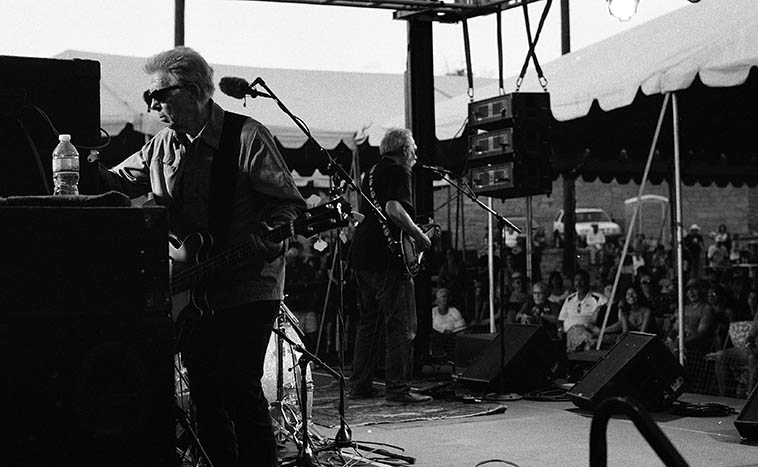 Jack Casady making some adjustments -- HOT TUNA at Madrid Ball Park, New Mexico, July 10, 2o16 -- Jorma out front ---- These guys were smoking, no histrionics, no rock god posturings, no jumping up & down (well, Jack did do a little of that, but it was all in fun) just pure hardcore psychedelic blues, and with the bass mixed nice and loud (something their record producers need to consider) -- I hope somebody recorded this one as it was one for the ages, nestled in a vale surrounded by hills dotted with junipers and pinon and a sunset on a lavish hot day (producers rented a canopy for all of us, thank gawd) -- photo by Mark Weber