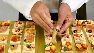 Mains de Cuisiniers qui décors des toast cocktail avec un cornet mayonnaise