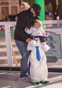 Ben Kleppinger/ben.kleppinger@amnews.com Casey McGuffey of Danville holds his daughter, 1-year-old Shelby, on a polar bear as they have fun in the rink.