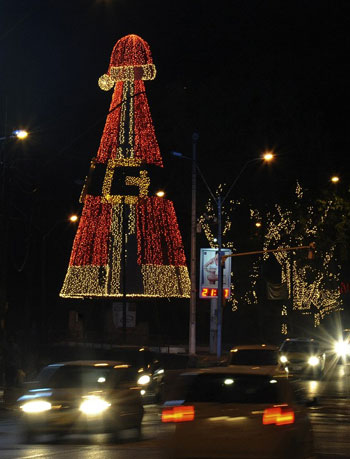 [Caption] Cars drive past a Christmas tree in Asuncion on December 22, 2013.