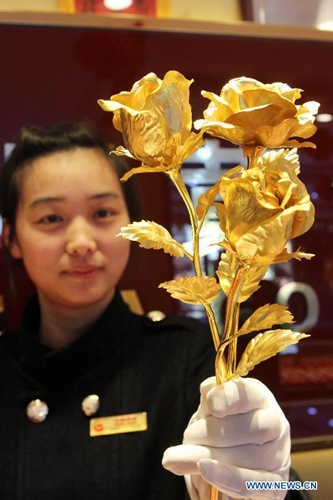 A salesgirl shows a gold rose at a gold shop in Lianyungang City, east China's Jiangsu Province, Feb. 9, 2014. As the valentine's day draws near, roses made of pure gold has become popular among customers despite of its high price. [Photo: Xinhua/Si Wei]
