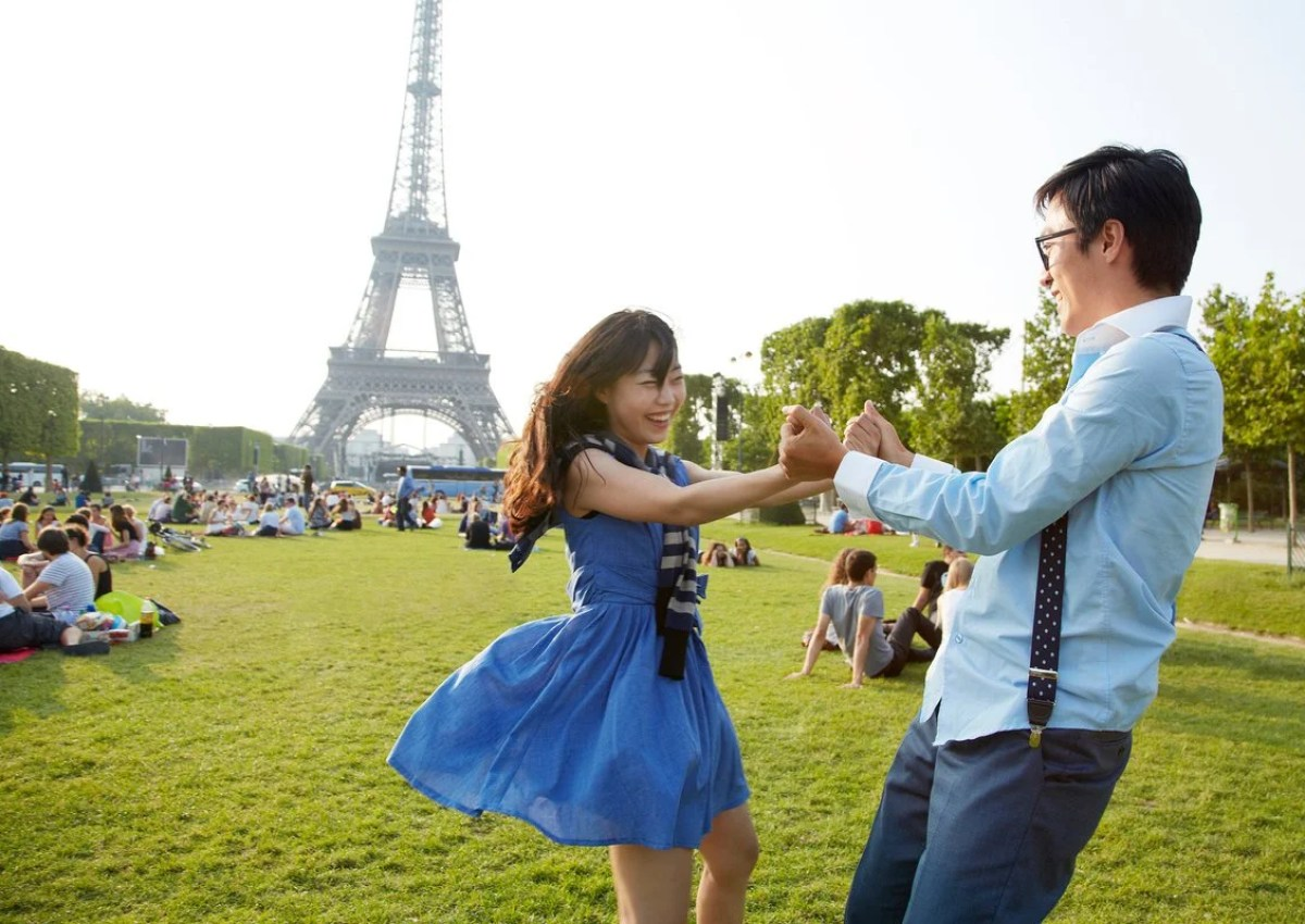 Two smiling people holding hands and standing in the grass in front of the Eiffel Tower in Paris, France.