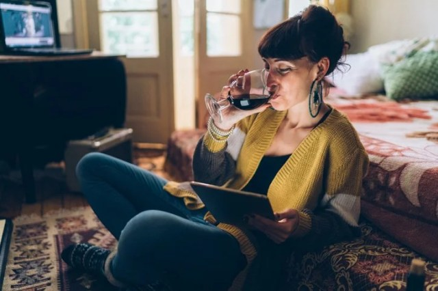 A woman sitting on the floor drinking wine while watching a movie on her tablet.
