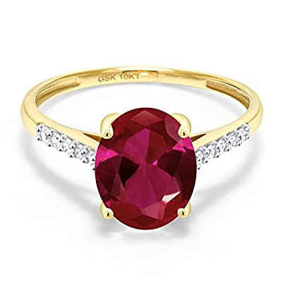 MEASUREMENTS: 10x8mm Oval Red Created Ruby, 1.3x1.3mm Round I - J Diamond. Total Carat Weight is 2.62 cttw. CRAFTED: in 10k Yellow Gold with 10k stamp. USA BASED COMPANY AND SERVICE: Our jewelry passes extensive quality checkpoints before being shipp...