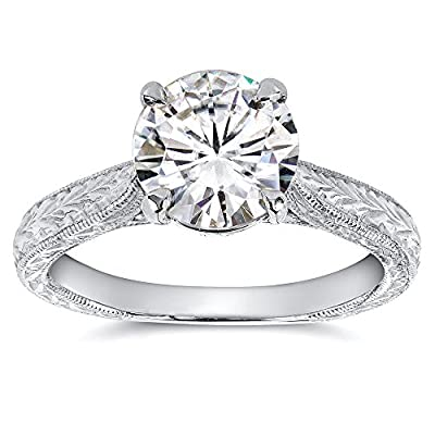 Center stone is a 7.5mm Genuine Kobelli Moissanite Features two small bezel-set diamonds on the ring profile Satisfaction Guaranteed. Return or Exchange Policy Within 30 Days Made in USA with Eco-Friendly 100% Conflict-Free Materials. Designed and ma...