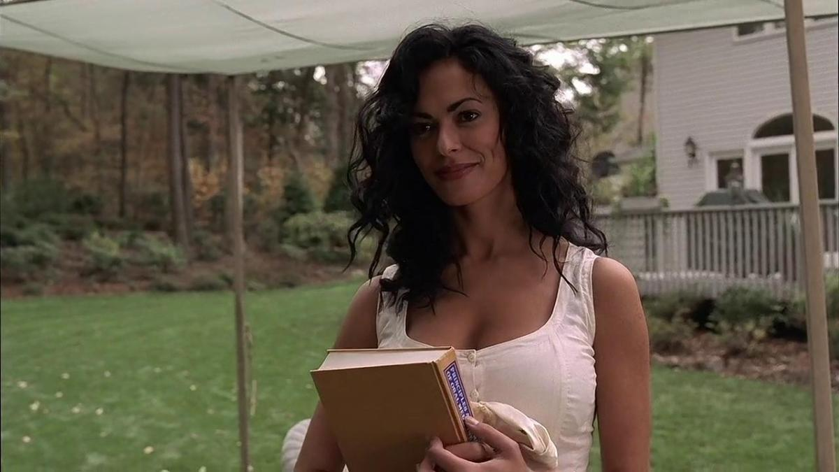 Isabella is introducing herself to Tony Soprano in the yard while holding a principles of oral surgery book.