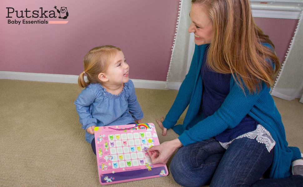 a girl and mom holding Putska potty training chart - unicorn theme