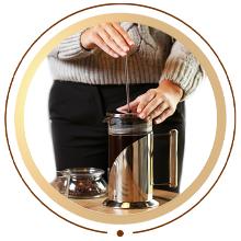Person steeping coffee inside glass coffee maker