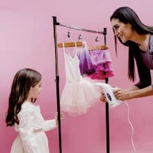 Mother showing her little daughter how to steam her ballet dress with an iron steamer
