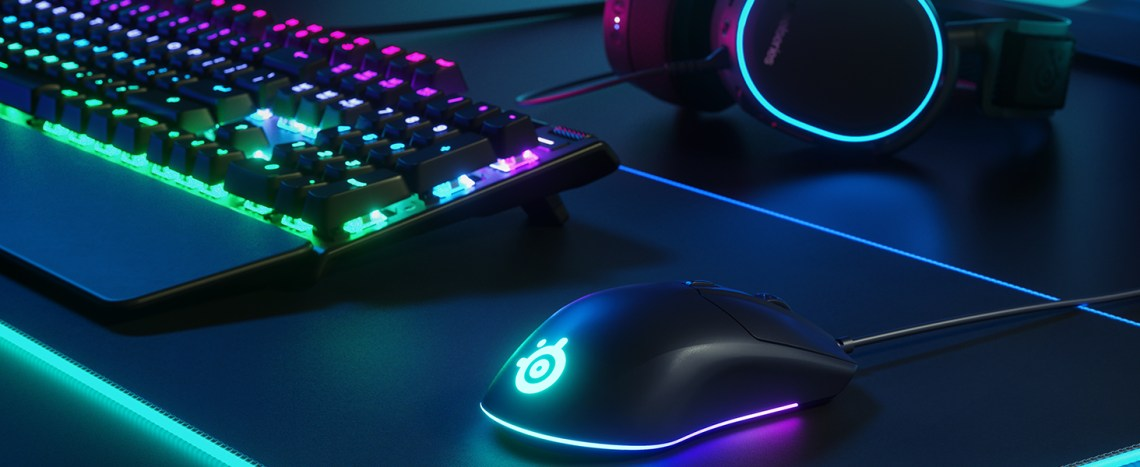 - SteelSeries desk setup with Rival 3 mouse, Apex keyboard, Arctis headset, and QcK Prism mousepad