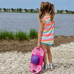 A girl carries her bouncing ball by a lake