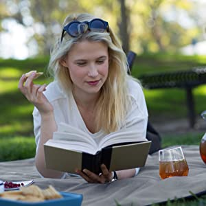 girl reading book on waterproof picnic blanket, eating food at park on top of wet grass, staying dry