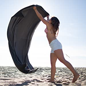 girl waving out outdoor waterproof picnic blanket to show how large this xl,extra large, blanket is