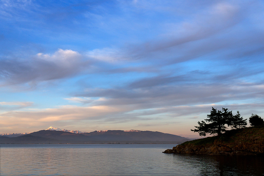 Sunset of Saddlebag Island with Mount Baker and Cascade Mountains across Padilla Bay
