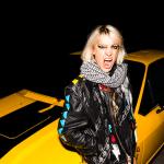 portrait de l'artiste suisse romande Evelinn Trouble devant une voiture jaune