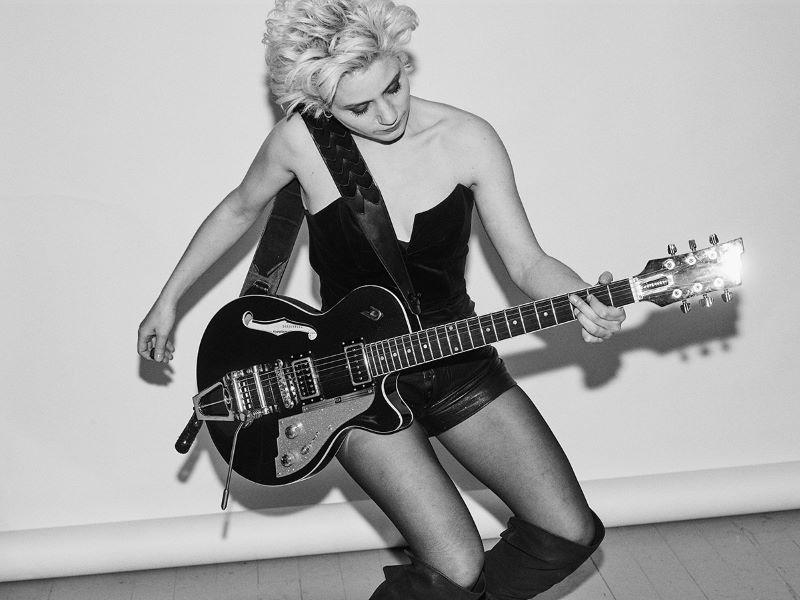 Portrait en noir et blanc de l'artiste Alice Animal avec sa guitare