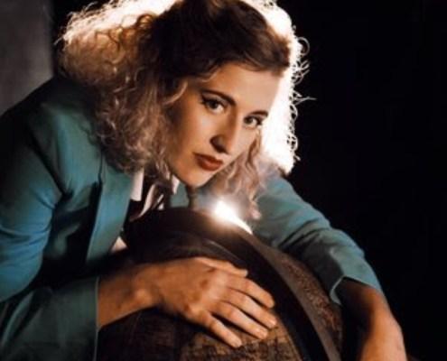 L'artiste Mary Bach est penchée sur un globe en tailleur bleu