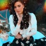 portrait posé de l'artiste MOGGY assise avec jupe à fleur et haut blanc
