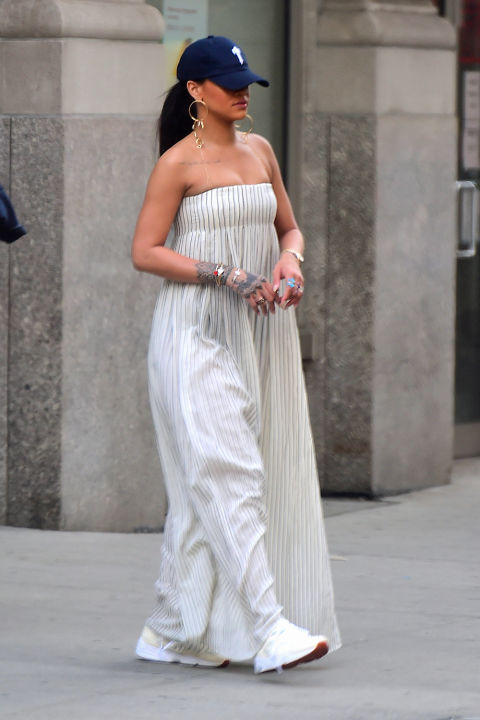 In the midst of a muggy New York day, RiRi stepped out wearing a billowy strapless maxi dress from Brock Collection with a baseball cap and white sneakers looking every bit casual-chic, as always.