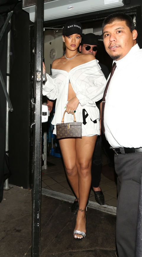 Out in West Hollywood, RiRi wore a white button-down top worn off the shoulders and unbuttoned on the bottom to show off her midriff. She paired it with white shorts, a mini Louis Vuitton bag, and strappy sandals.