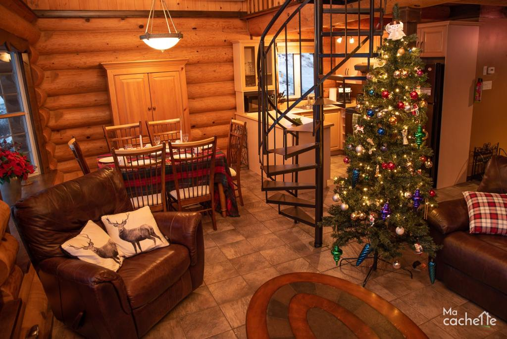 Petit Domaine forêt d'eau - Chalet bois rond à louer au Lac Simon - Salon et salle à mangé décorée pour le temps des fêtes avec sapin de Noël