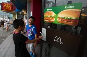 Boys open the door to a McDonald's restaurant in Beijing