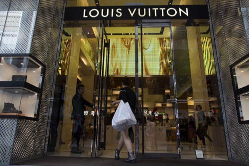 A shopper enters a Louis Vuitton in Hong Kong