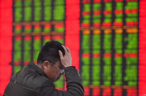 An investor holds his head as he monitors stock prices at a brokerage house in Fuyang in central China's Anhui province yesterday