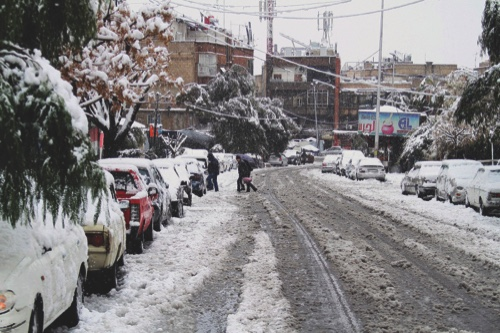 People walk across a snow-blanketed street in Damascus, Syria