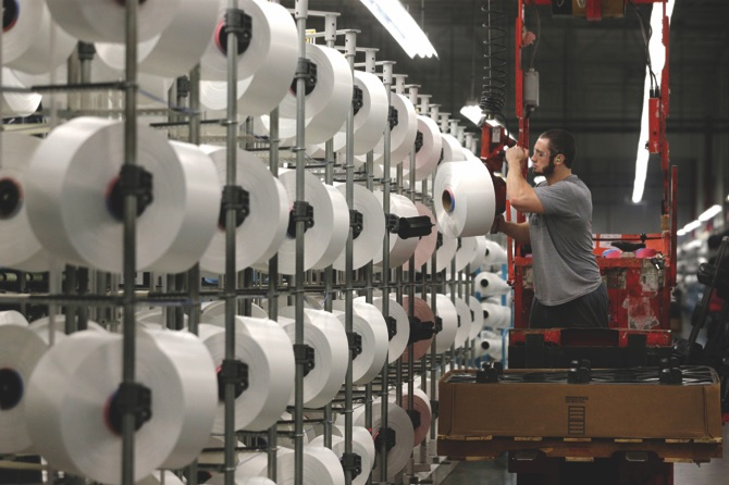 A worker loads spools of thread