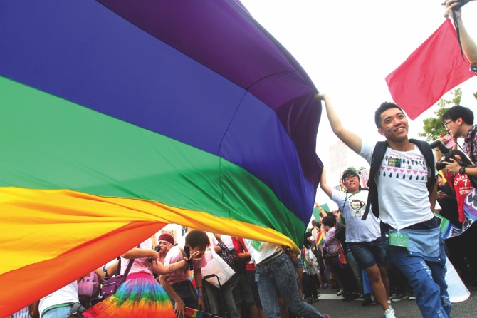 Participants revel through a street during a gay and lesbian parade in Taipei