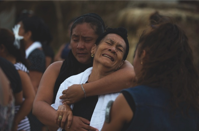 Mourners grieve at a funeral service for 90-year-old Hermilo Martinez