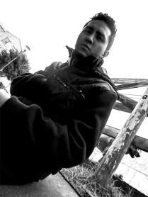 """Josep Moreno, (Bogotá 1995). Comunicador gráfico e ilustrador. """"Bahkyek"""" es un chamán muisca, un personaje creado con el fin de ser un guardián de humedales. Bahkyek tiene un cuerpo delgado y lleno de escamas, le gusta coleccionar piezas de cerámica y conchas de caracol, aparece sentado sobre un trono de rocas, cerámica y oro, su fuerza es una retroalimentación con la vida del humedal, Bahkyek lo restaura, y con el tiempo el humedal lo sana a él. La ilustración está realizada con lápices de colores sobre papel durex, tamaño 1/4 e intenta realzar la identidad ancestral ligada al municipo de Suacha."""