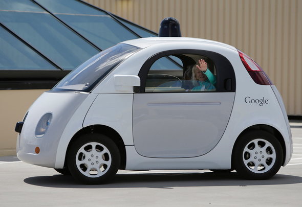 Judy Larsen waves during a demonstration ride of the two-seater prototype of Google's self-driving car at Google in Mountain View, Calif., on Wednesday, May 13, 2015. (LiPo Ching/Bay Area News Group)