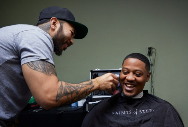 Jerome Villanueva (left), a Bay Area barber who volunteers with Saints of Steel, gives Frank Clay a haircut at a pop-up event in San Francisco.