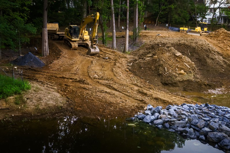 Heavy machinery used to repair banks of stream during a stream restoration project