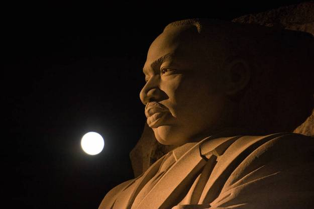 The moon, or supermoon, is seen as it sets over the Martin Luther King Jr. Memorial