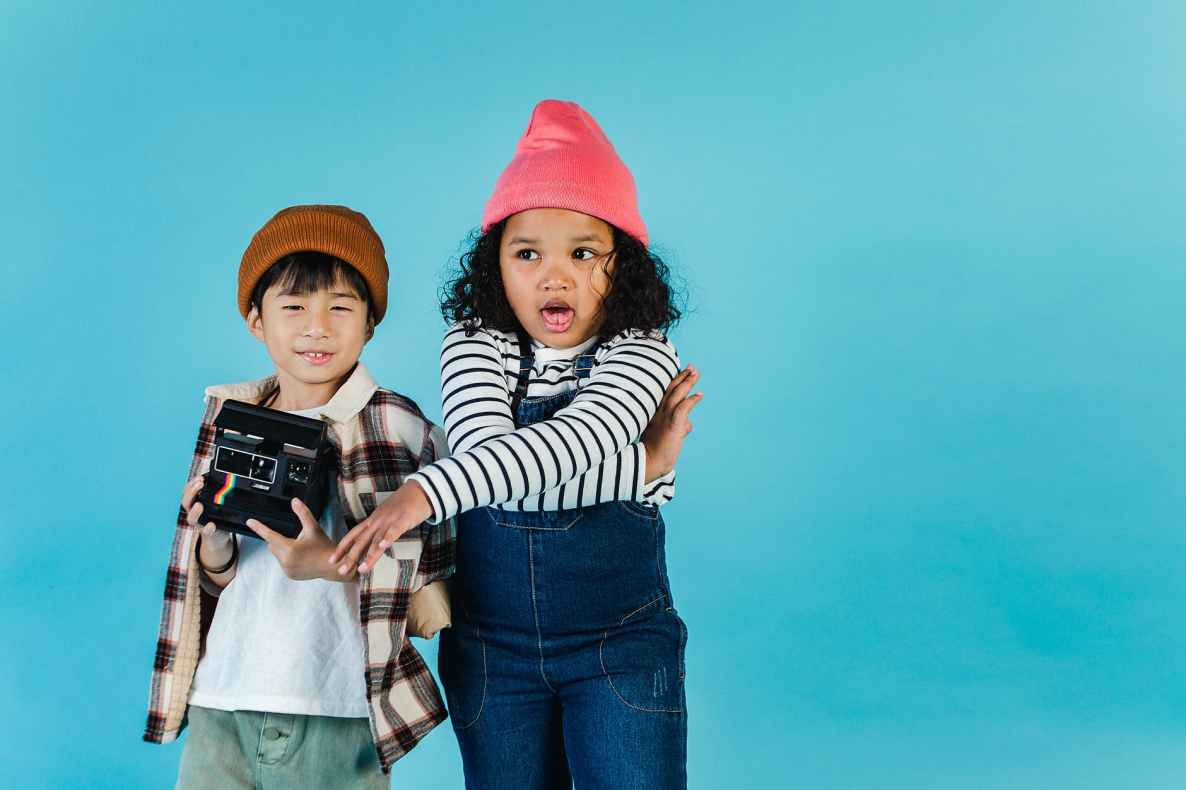 little multiethnic friends with retro photo camera standing together