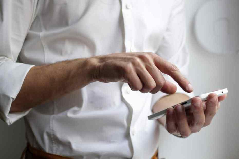 Na imagem, home de camisa branca indo tocar no celular