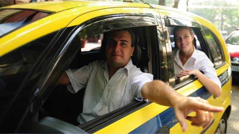 Taxista sorrindo com passageira no banco de trás